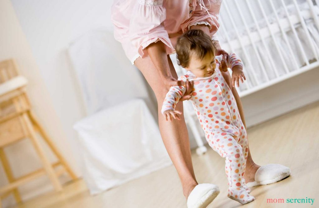 Mom helping a baby learn how to walk with great baby walking tips