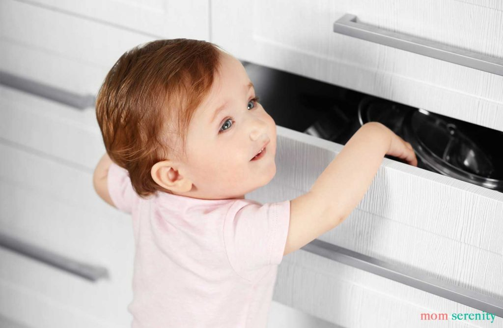 Baby reaching into drawer that isn't baby proofed